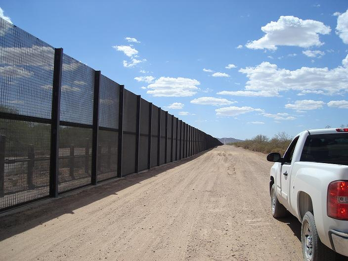 A white truck drives parellel to the tall black U.S. - Mexico border fence.